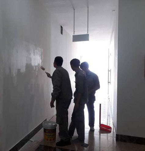Công nhân đang sơn lại tường, nơi vừa tháo biển hiệu của trung tâm MST. (Ảnh: Tùng Lâm).
