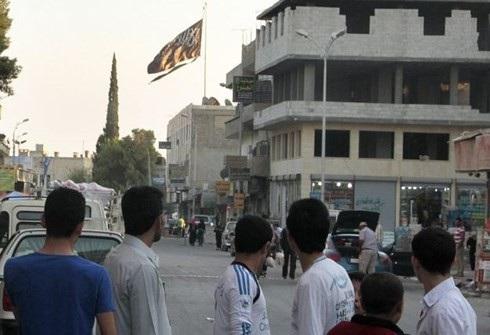Cờ đen của tổ chức khủng bố IS xuất hiện tại Raqqa khi tổ chức này nắm chặt thành phố này. Ảnh: AFP.