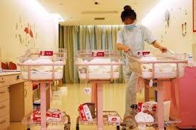 Một nhân viên của trung tâm ở cữ đang chăm sóc những bé sơ sinh. (Nguồn: AFP)