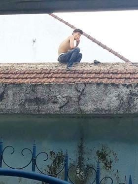 Nam thanh niên nghi ngáo đá ngồi trên nóc nhà (ảnh: Minh Đức)