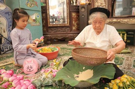 Bà Nguyễn Thị Dần tỉ mẩn tách gạo sen để ướp trà. Ảnh: T.N