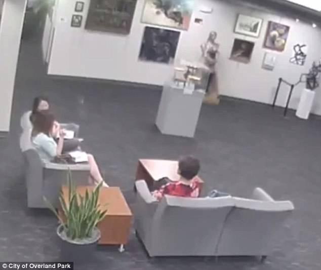 Cậu bé chạy lại ôm bức tượng ở góc phòng trong khi mẹ ngồi nói chuyện với bạn bè ở ghế sofa.