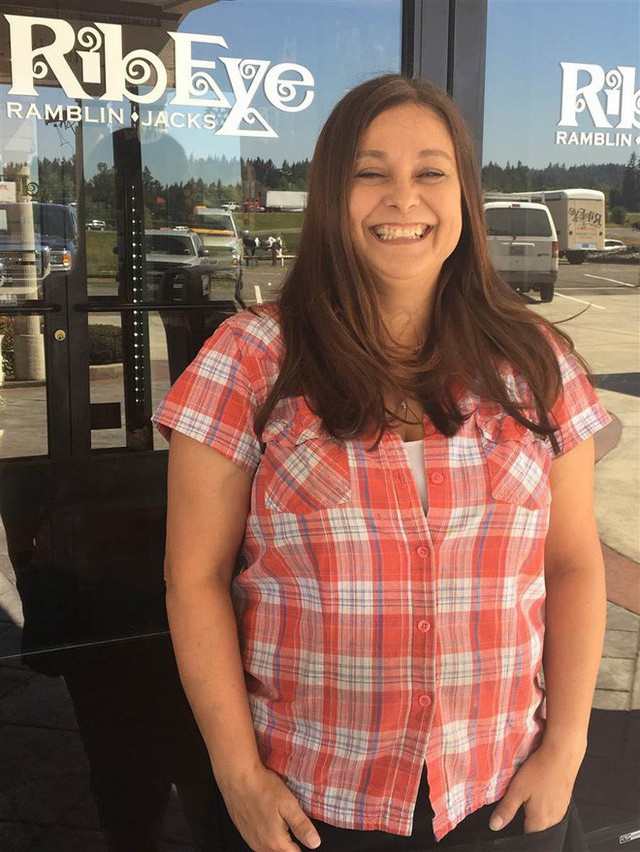 Nữ nhân viên phục vụ đứng trước nhà hàng mình làm việc
