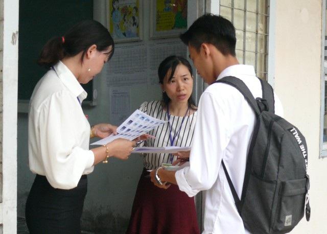 Cán bộ coi thi ở Cà Mau kiểm tra, đối chiếu thông tin thí sinh dự thi chiều ngày 24/6. (Ảnh: H.H)