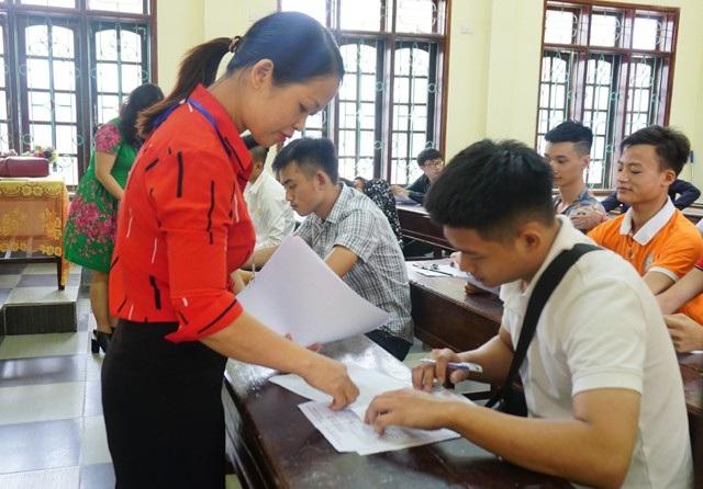 Giám thị đối chiếu các thông tin trong giấy báo dự thi của thí sinh. (Ảnh: Hoàng Lam)