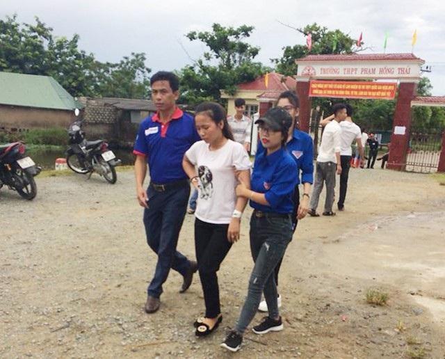 Thí sinh Trần Thị Ngọc Ánh được các tình nguyện viên hỗ trợ đưa ra khỏi điểm thi do sức khỏe không đảm bảo để tham dự kỳ thi THPT quốc gia (ảnh Cao Hằng)