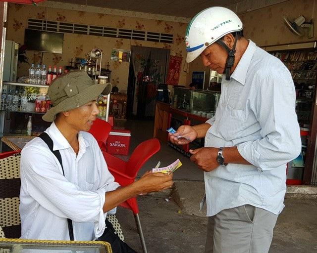Anh Kim Thái (bên trái) vừa bán vé số vừa trau dồi kiến thức. (Ảnh: Bạch Dương)