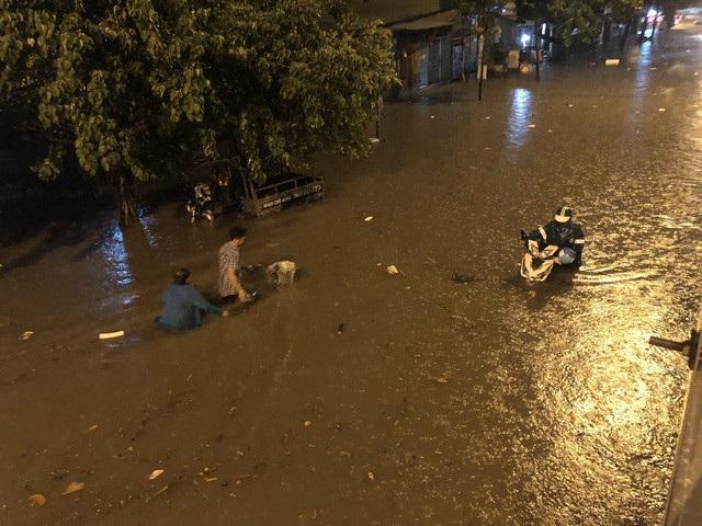 Sau cơn mưa lớn rạng sáng 2/6, nhiều tuyến đường ở trung tâm Sài Gòn đã bị ngập lênh láng, trong đó đường Nguyễn Hữu Cảnh (quận Bình Thạnh) bị ngập đến yên xe máy, mặc dù UBND TPHCM đã thuê máy bơm chống ngập cho tuyến đường này. (Ảnh: Đình Thảo)