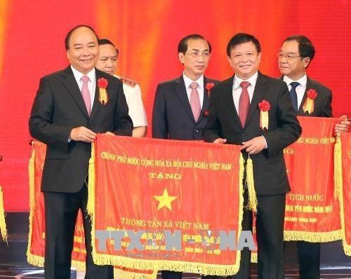 Thủ tướng Nguyễn Xuân Phúc tặng cờ thi đua của Chính phủ cho Thông tấn xã Việt Nam, đơn vị dẫn đầu phong trào thi đua yêu nước năm 2017. (Ảnh: Doãn Tấn/TTXVN)
