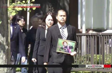 Anh Lê Văn Hào mang di ảnh của con tới dự phiên toà