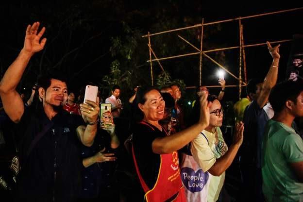 Người dân vui mừng vẫy chào khi xe cứu thương chở cầu thủ được giải cứu đi qua vào tối 9/7. (Ảnh: Getty)