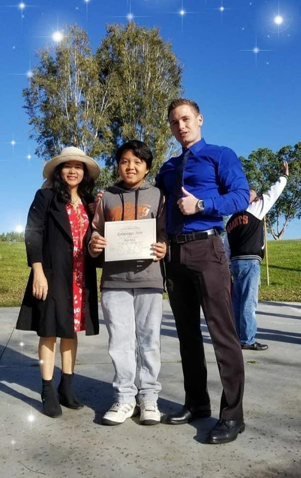 """Xuân Hòa và mẹ chụp hình lưu niệm cùng thầy hiệu trưởng khi nhận bằng khen """"Language Arts""""."""