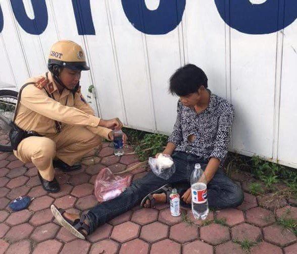 Các chiến sĩ CSGT giúp đỡ anh Hoạt khi bất tỉnh trên đường.
