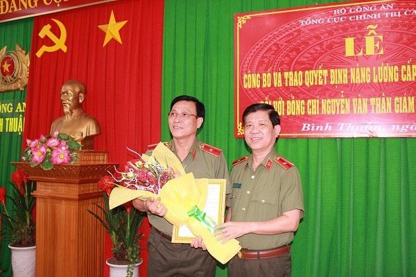 Thiếu tướng Nguyễn Văn Thân (bên trái) được tặng hoa trong ngày nhận quyết định tăng bậc lương cấp thiếu tướng (ảnh: Cổng thông tin điện tử tỉnh Bình Thuận)