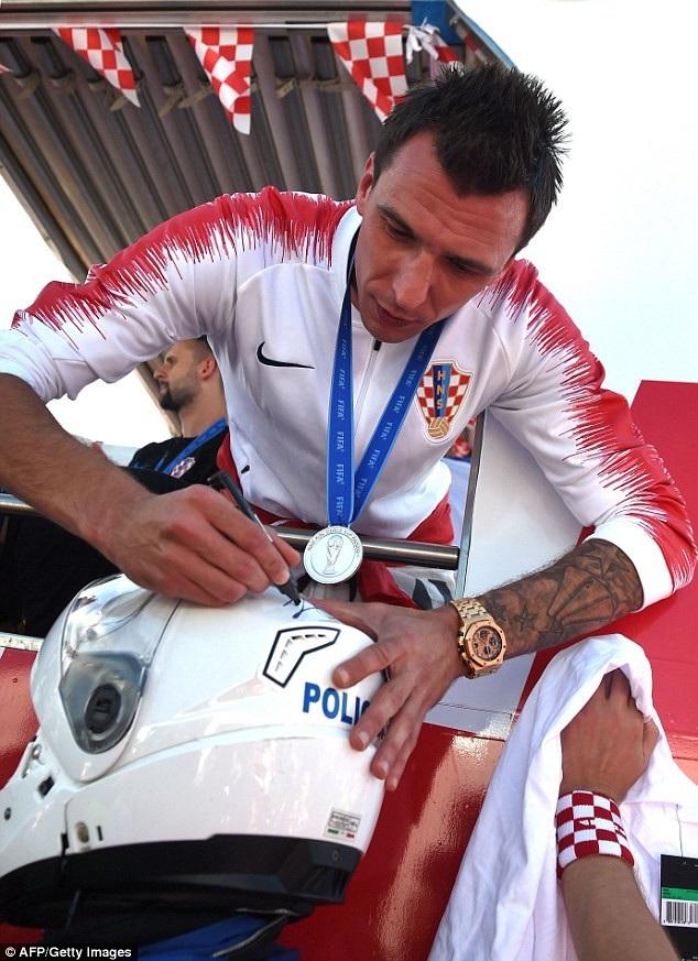Mario Mandzukic ký tặng lên mũ bảo hiểm của nhân viên cảnh sát tháp tùng đoàn