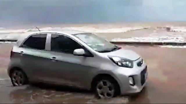 Một chiếc xe ô tô chạy trên đường đê Quất Lâm ngập trong nước biển