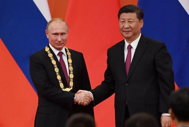 Chủ tịch Trung Quốc Tập Cận Bình trao huân chương hữu nghị cho Tổng thống Nga Vladimir Putin. (Ảnh: Reuters)