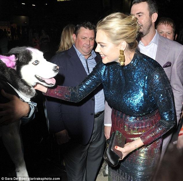 Siêu mẫu vui vẻ chào hỏi 1 chú cún bên ngoài phòng tiệc