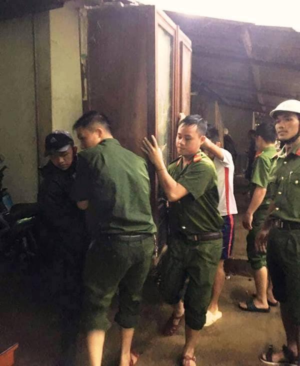 Các chiến sĩ, cán bộ công an huyện Kỳ Sơn dầm mưa để vận chuyển đồ đạc cho dân.