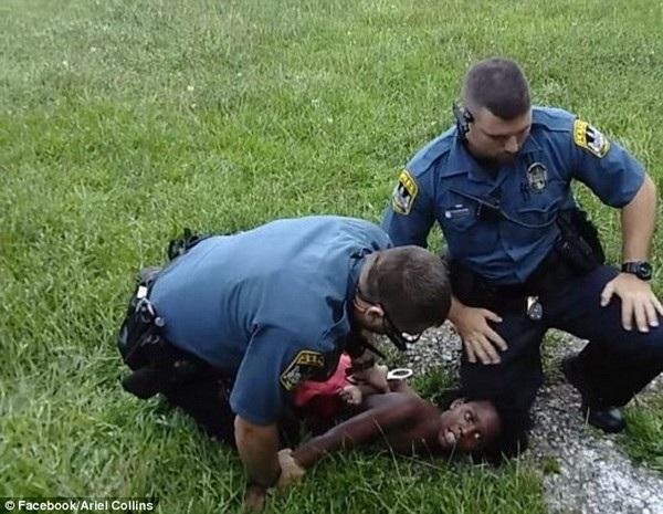 Cậu bé 10 tuổi bị cảnh sát đè xuống đất, sự hoảng sợ bộc lộ trên gương mặt cậu bé