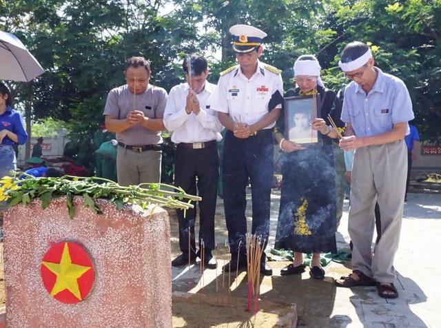 Thân nhân liệt sĩ Nguyễn Đình Quảng trước phần mộ an táng tại Nghĩa trang liệt sĩ huyện Nghi Lộc (Nghệ An).