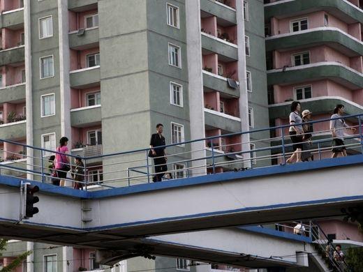 Người dân đi bộ trên một cây cầu đi bộ nối giữa những tòa nhà chung cư. Những khu chung cư là nơi ở khá phổ biến cho người dân sống tại thủ đô của Triều Tiên.