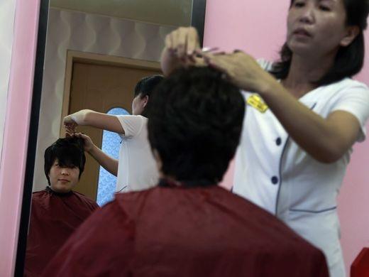 Một phụ nữ cắt tóc tại một tiệm làm đầu ngay bên trong khuôn viên của công viên nước Munsu ở Bình Nhưỡng. Công viên nước Munsu được ví như Disneyland, nằm tại trung tâm thủ đô của Triều Tiên, đón cả du khách nước ngoài tới giải trí.