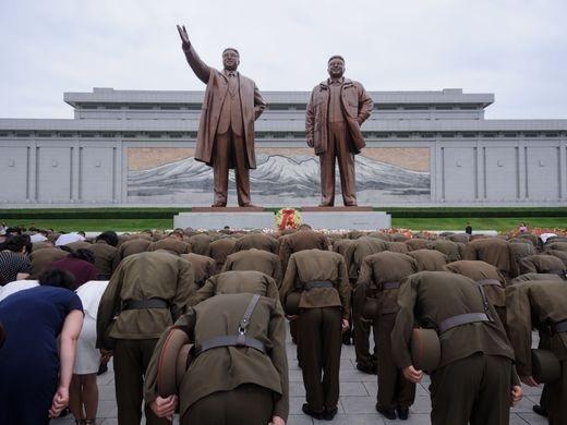 Các binh sỹ của quân đội nhân dân Triều Tiên đang cúi đầu trước những bức tượng hai vị lãnh đạo Kim ll Sung và Kim Jong ll trong lễ kỷ niệm 24 năm ngày mất của ông Kim ll Sung. Hình ảnh chụp trên đồi Mansu ở Bình Nhưỡng hôm 8/7.
