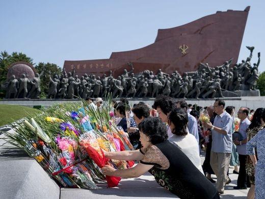 Người dân đặt hoa tươi bày tỏ sự kính trọng trước tượng bằng đồng của hai vị lãnh đạo Kim ll Sung và Kim Jong ll trên đồi Munsu.