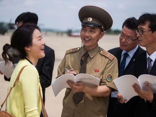 Nữ phóng viên người Hàn Quốc đang vui vẻ trò chuyện khi được những quan chức ở Triều Tiên kiểm tra danh tính tại sân bay quốc tế Sunan, Bình Nhưỡng.