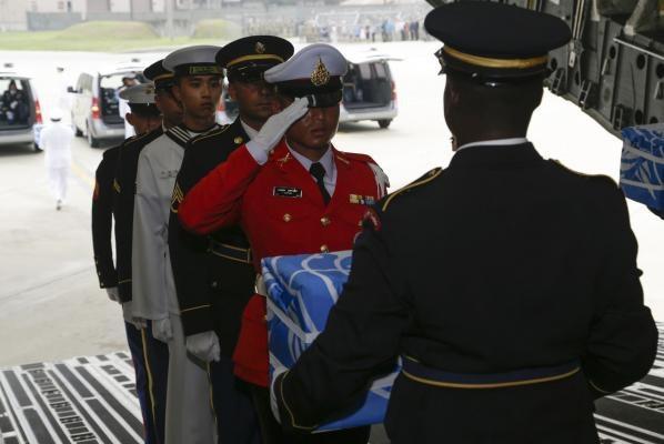 Những người lính danh dự đưa từng bộ hài cốt ra khỏi máy bay vận tải sau khi máy bay hạ cánh xuống căn cứ không quân Osan. (Ảnh: Bộ Quốc phòng Mỹ)