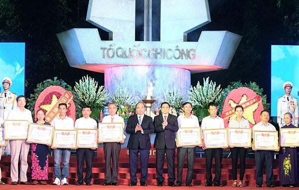 Thủ tướng Nguyễn Xuân Phúc và Trưởng ban Tổ chức Trung ương Phạm Minh Chính trao Bằng Tổ quốc ghi công cho thân nhân gia đình các liệt sĩ. Ảnh: VGP