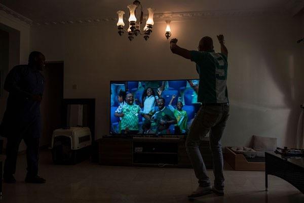 Một cổ động viên Nigeria ăn mừng chiến thắng 2-0 của đội nhà trước đội tuyển Iceland tại vòng bảng World Cup khi đang theo dõi trước màn hình TV tại nhà riêng.