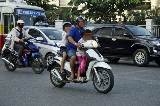 Phụ huynh chở con em bằng xe máy đi học - hình ảnh thường thấy ở các thành phố lớn