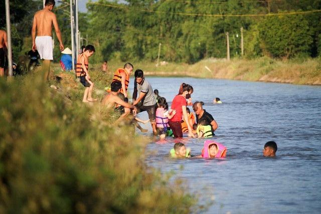 Mương nước tưới tiêu nông nghiệp ở xã Ninh Sở (Thường Tín, Hà Nội) những ngày này trở thành bể bơi khổng lồ thu hút nhiều người đến tắm mát giải nhiệt. (Ảnh: Toàn Vũ)