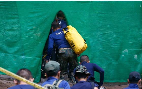 Vào 10 giờ sáng nay theo giờ địa phương, 18 thợ lặn, gồm 13 thợ lặn nước ngoài và 5 thợ lặn Thái Lan, đã tiến vào hang Tham Luang ở tỉnh Chiang Rai để bắt đầu chiến dịch giải cứu các thành viên trong đội bóng bị mắc kẹt và huấn luyện viên. Trong ảnh: Các thành viên của lực lượng cứu hộ xuất hiện tại khu vực gần hang Tham Luang. (Ảnh: AP)