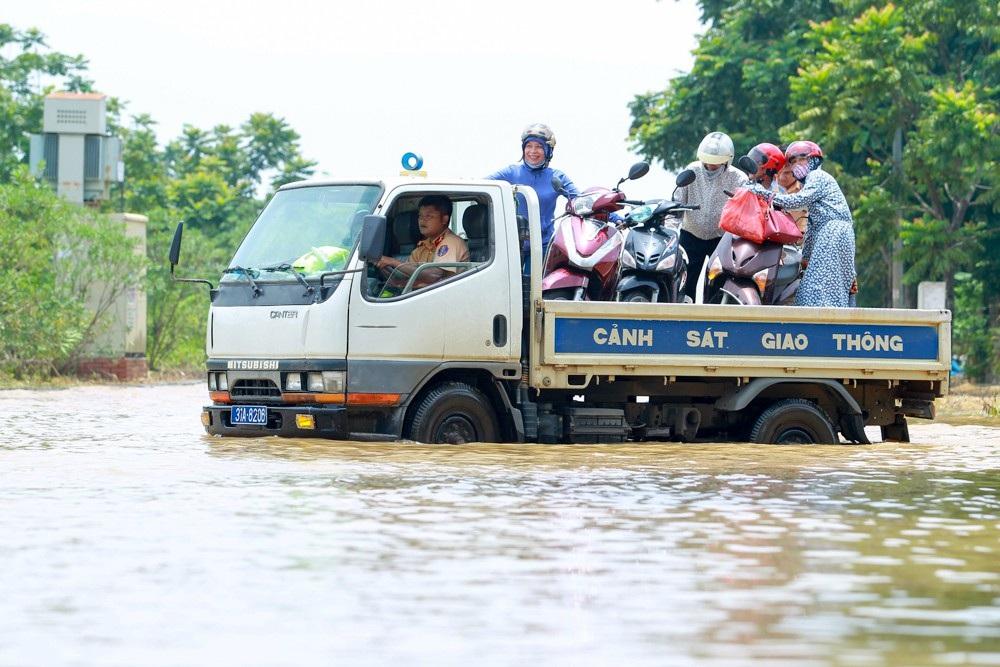 Người và xe người dân được vận chuyển qua đoạn ngập sâu.