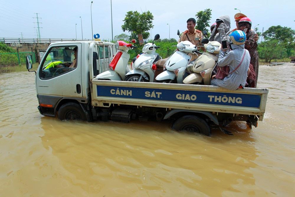 Chị Nguyễn Thị Hạ (Quốc Oai, Hà Nội) cho biết, đoạn đường này ngập đã bị chia cách nhiều ngày, từ khi có lực lượng CSGT ra giúp người dân, chi mới có thể đi qua.