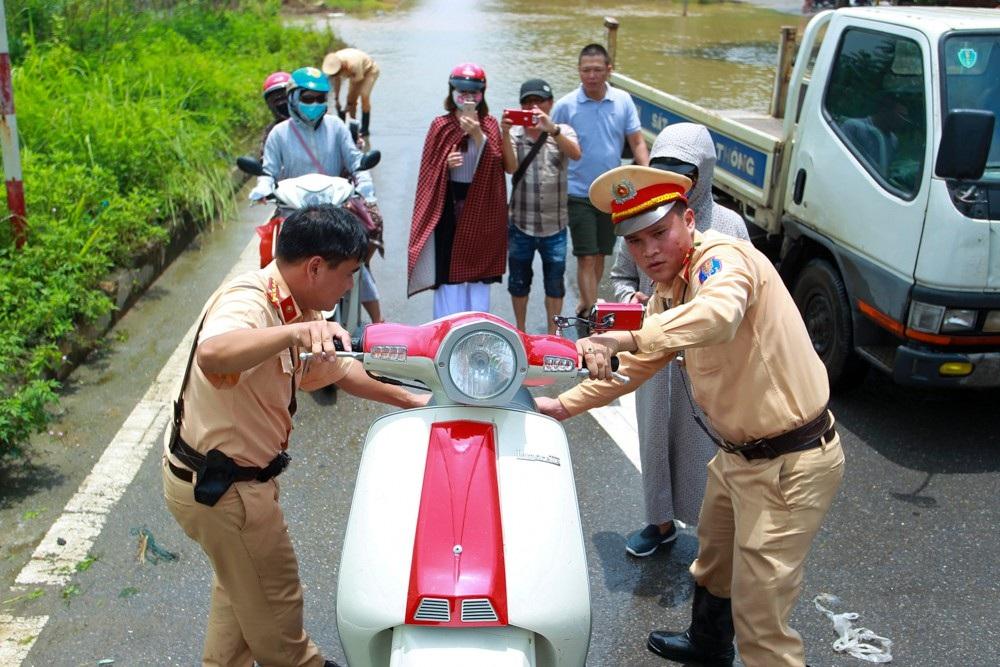 Hai cán bộ CSGT đội 11 dắt phương tiện của người dân lên xe chung chuyển qua đoạn ngập.