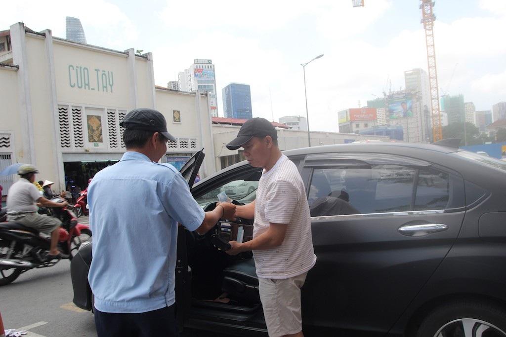 Nhân viên thu tiền của khách để đặt điểm đỗ xe