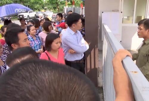 Phụ huynh tụ tập trước cổng trường Tiểu học Cao Bá Quát để phản đối việc phân tuyến (Ảnh: N. Hà).