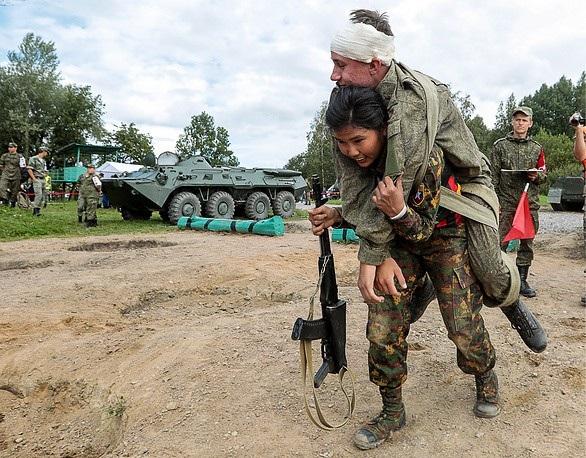 Một nữ binh sĩ đội Myanmar cõng đồng đội hoàn thành phần thi quân y tiếp sức. (Ảnh: TASS)