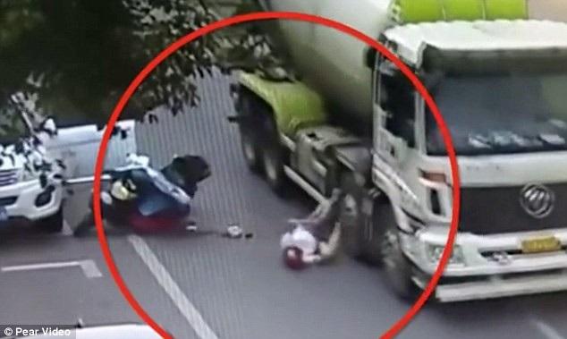Khoảnh khắc Zhu bị cuốn vào bánh xe tải đang lưu thông trên đường (Ảnh: Pear Video)