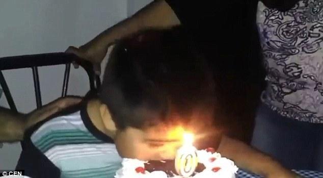 Cậu bé vội vã cúi đầu ăn bánh