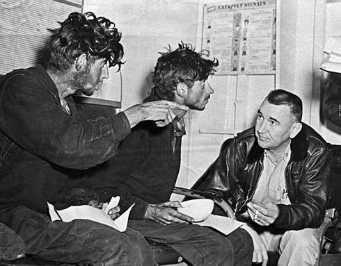 Filipp Poplavsky (trái) và Askhat Ziganshin (giữa) thuật lại cảnh ngộ của họ với một thủy thủ Mỹ sau khi họ được đưa lên tàu sân bay Kearsarge. Ảnh: Sputnik.