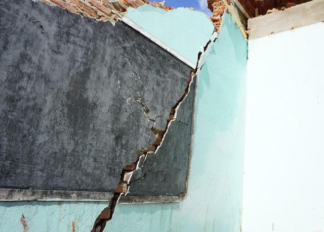 Bức tường còn lại bị đứt gãy, có thể đổ sập bất cứ lúc nào, đe dọa sự an toàn của dãy nhà bếp làm bằng gỗ sát đó