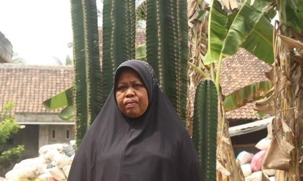 Bà Benah đứng bên ngoài ngôi nhà tại Indonesia (Ảnh: Guardian)
