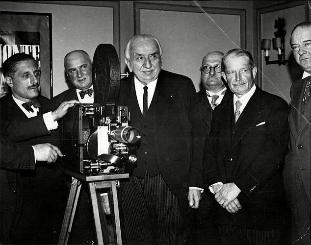Nhà làm phim Louis Lumiere đứng bên cạnh chiếc máy quay phim sơ khai của mình.