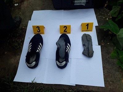 Lực lượng chức năng tìm được đôi giày cùng tất được cho là của hung thủ gần hiện trường gây án (Ảnh: Công an cung cấp).