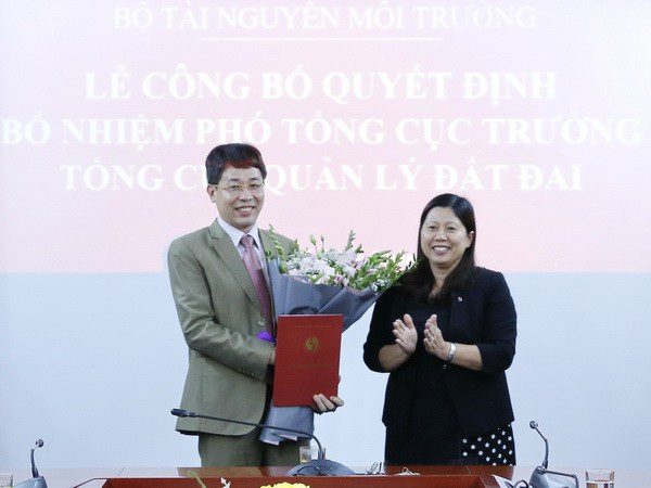 Thứ trưởng Nguyễn Thị Phương Hoa trao quyết định và tặng hoa chúc mừng ông Mai Văn Phấn (Ảnh: Bộ TN-MT).